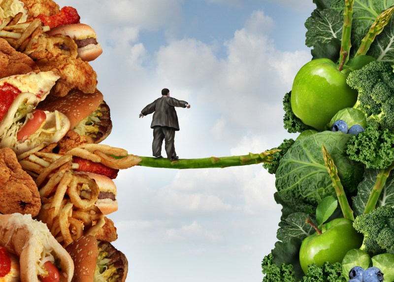 Diet+change+healthy+lifestyle+concept+and+having+the+courage+to+accept+the+challenge+of+losing+weight+and+fighting+obesity+and+diabetes+as+an+overweight+person+walking+on+a+highwire+asparagus+from+fatty+food+towards+vegetables+and+fruit.