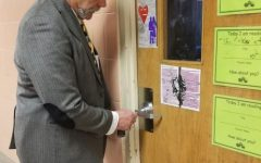 Mr. Campbell tests a door for security.